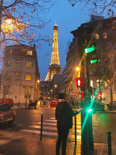 The Eiffel tower at night from across a Parisienne street